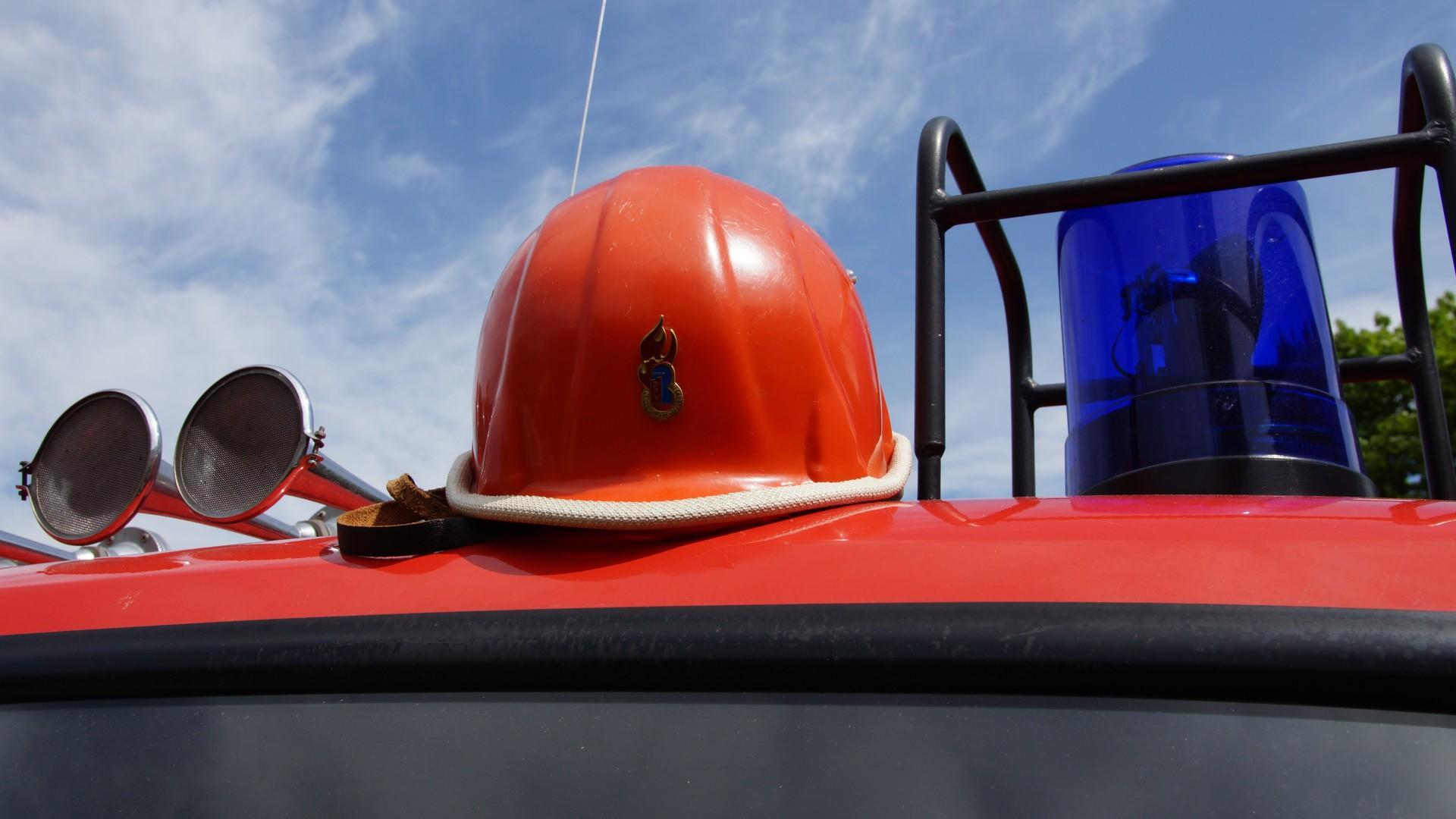 Helm der Deutschen Jugendfeuerwehr auf Feuerwehrauto neben Sirene